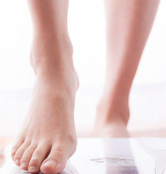 underweight woman stepping on scales